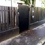 Palissade bois teinté noir, porte acier perforé laqué noir